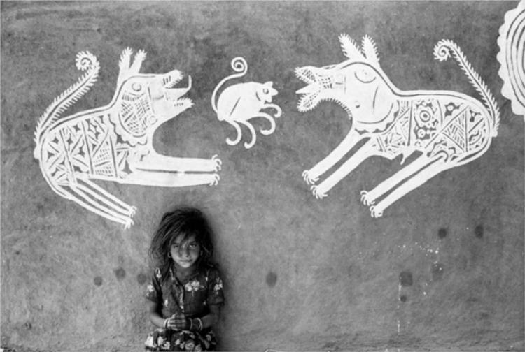 A young girl in front of mandana paintings, Rajasthan - Jyoti Bhatt